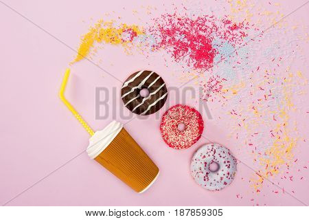 Top View Of Coffee Cup And Variety Frosted Donuts Isolated On Pink. Donuts And Coffee Background