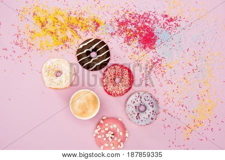 Top View Of Donuts With Different Sweet Glaze, Sprinkles And Cup Of Coffee On Pink. Donuts Chocolate