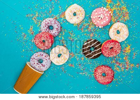 Overhead View Of Scattered Several Donuts With Various Glaze. Donuts Isolated On Blue Background