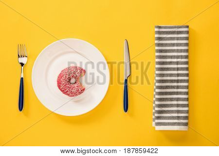 Overhead View Of Bitten Donut With Pink Glaze In Plate And Napkin  Isolated On Yellow. Background In