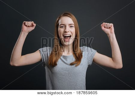 I did it. Cute joyful young lady showing her emotions while working on professional photoshoot and standing isolated on grey background