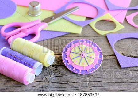 Felt circle flower decorated with beads. Handmade flower felt crafts, scissors, thread, colored felt sheets, thimble on vintage wooden background. Simple and quick felt crafts. Teaching kids to sew