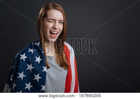 Playful mood. Cool creative proud girl making a patriotic photoshoot and posing with a flag while standing isolated on grey background