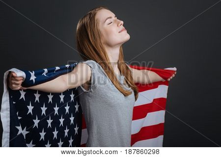 Living the dream. Cute lively dreamy woman standing isolated on grey background and holding the flag in her hands while looking dreamy
