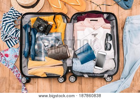 Overhead view of traveler's accessories organized in open luggage on wooden floor