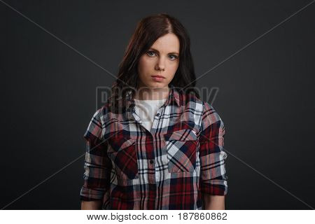 Young and serious. Beautiful stunning resolute lady posing for a photographer during the photoshoot while showing emotions and standing isolated on grey background