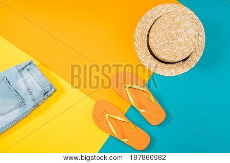 Summer vacation background with orange flip flops denim trousers and hat on colored copy space