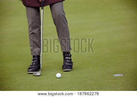 Unrecognizable person standing and preparing to hit the ball to hole. Horizontal outdoors shot.