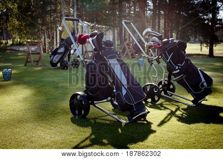 The trolleys in golf club with bags containing golf bats and equipment.