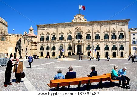 VALLETTA, MALTA - MARCH 30, 2017 - View of the Auberge de Castille in Castille Square with a statue of Manuel Dimech in the foreground and tourists sitting on a bench Valletta Malta Europe, March 30, 2017.