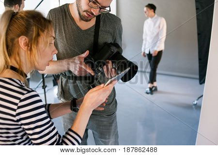 Photographer discussing with art coordinator. Man with camera communicate with photoshoot director during the studio session. Production of commercials backstage