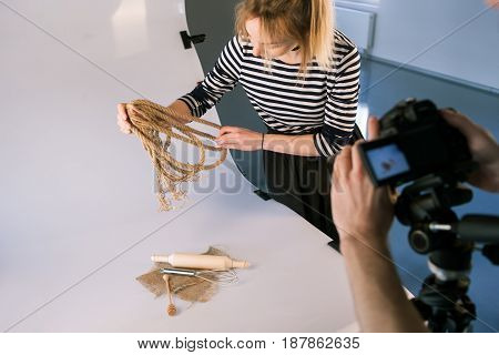 Handmade still life professional photoshoot. Unrecognizable photographer taking shots of domestic decor. Backstage of photo session with assistant.
