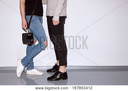 Unrecognizable hipsters with digital camera on belt near white wall. Female photographer and male model posing for photo. Friendship of sexes, lifestyle, leisure, hobby concept