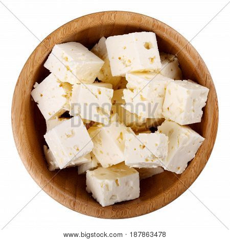 Wooden bowl of diced soft cheese isolated on white background Top view