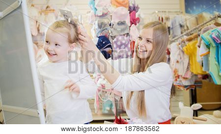 Shopping for kids - mother and daughter choose a accessorise in front of the mirror