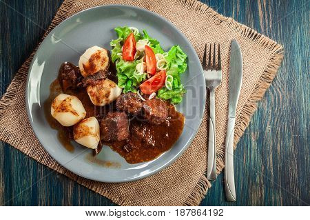 Pork Meat Stew Served With Potatoes And Vegetable Salad