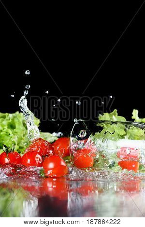 Red Fresh Cherry Tomatoes And Green Lettuce In Water  Isolated On Black, Harvest Vegetables And Leaf