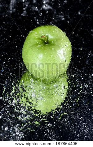 Green Apple In Water With Reflection On Black With Copy Space