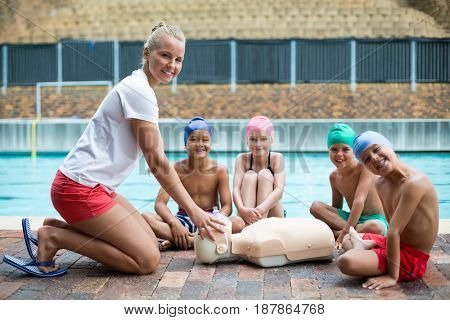 Portrait of children and instructor during rescue training at poolside