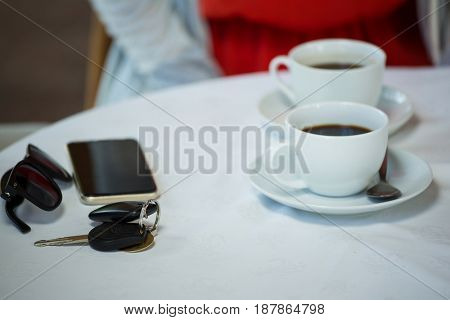 High angle view of coffee cups and personal accessories on cafe table