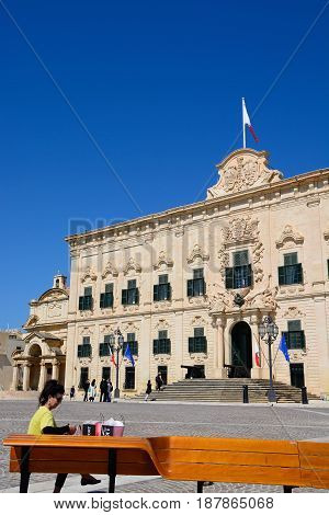 VALLETTA, MALTA - MARCH 30, 2017 - View of the Auberge de Castille in Castille Square with a woman sitting on a bench looking at her shopping in the foreground Valletta Malta Europe, March 30, 2017.