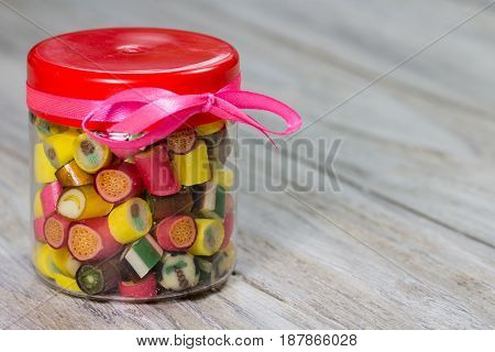 Many colorful candies in closed glass jar with pink ribbon on it wooden background