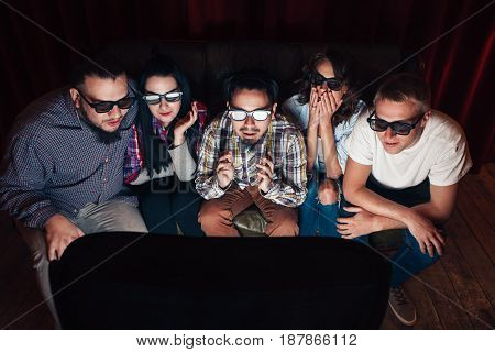 Young people in 3d glasses watch tv on couch. Five friends amazed by exciting effects of new technologies.