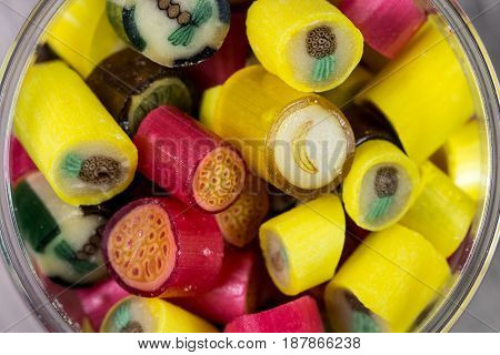 Many sweet colorful candies in opened glass jar closeup top view