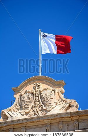 Maltese flag and coast of arms on top of the Auberge de Castille in Castille Square Valletta Malta Europe.
