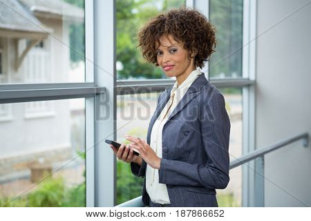 Portrait of businesswoman using mobile phone at conference centre