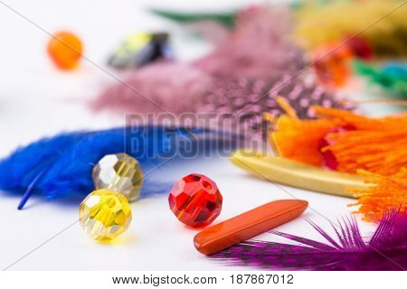 Glass beads colored feathers tassel earings on white background closeup. Selective focus.