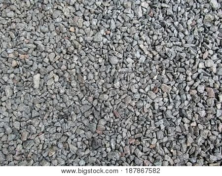 Abstract gray and beige crushed stone background - top view. Gravel poured in a uniform even layer