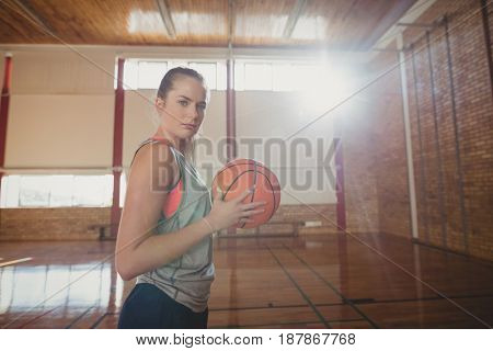 Determined high school girl standing with basketball in the court