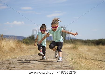 Portrait of little girls in similar wear jumping and running along stone path in park in sunlight.