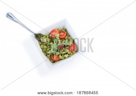High angle view of pasta salad in bowl with fork against white background
