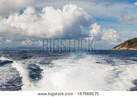 travel, seascape and nature concept - sea or indian ocean and trace on water of boat leaving seychelles