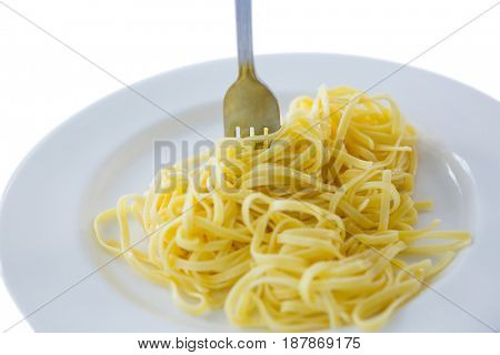 Close-up of spaghetti in plate with fork on white background