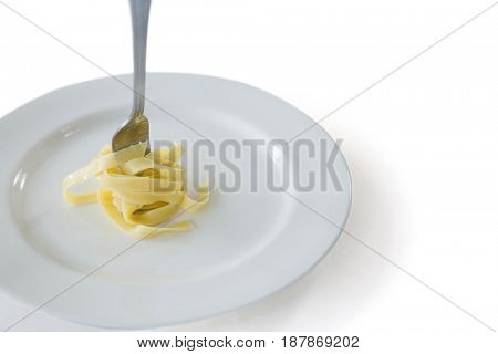 Close-up of spaghetti rolled up in fork with plate on white background