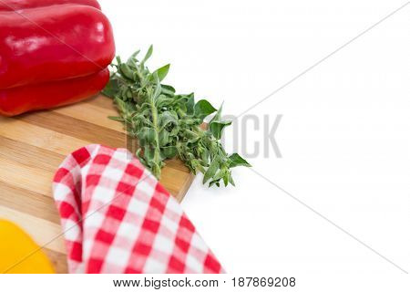 Close up of herb and bell pepper by napkin on cutting board against white background