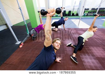 fitness, sport and training concept - group of people working out with dumbbells in gym