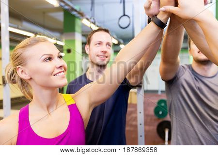 fitness, sport and teamwork concept - group of happy people or friends making high five in gym