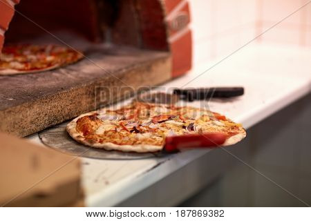 food, italian kitchen, culinary and cooking concept - baked pizza on peel and oven at pizzeria