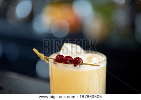 alcohol drinks and luxury concept - close up of cocktail glass with cherries at bar