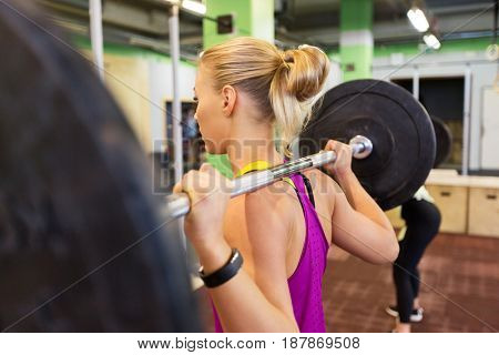 fitness, sport and people concept - woman with barbell at group training in gym