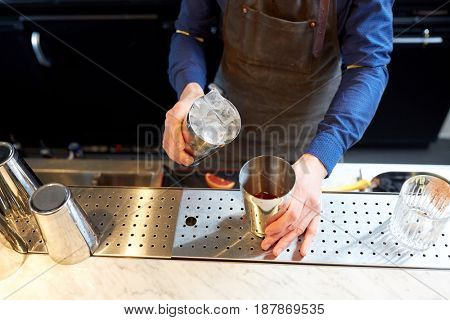 alcohol drinks, people and luxury concept - bartender adding ice into shaker preparing cocktail at bar