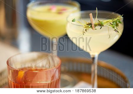 alcohol drinks and luxury concept - tray with glasses of cocktails at bar