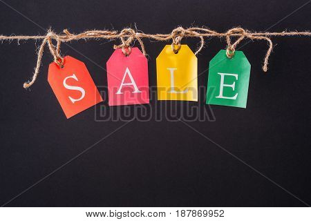Close-up View Of Colorful Sale Sign On Tags Hanging On Rope Isolated On Black, Offer Sale Tags