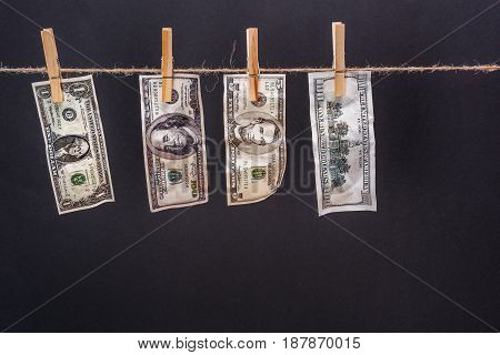 Close-up View Of Dollar Banknotes Hanging On Rope Isolated On Black