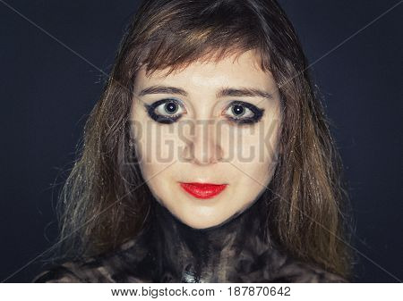 Teenager girl's face with bright makeup on dark background