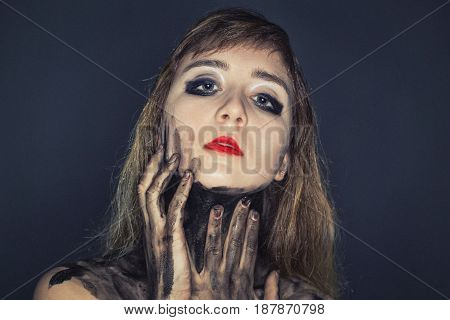 Teenager girl touching her dirty neck on dark background